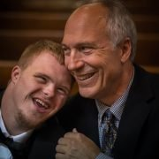 young man with Down sydrome and older man sitting closely together in church pews and smiling