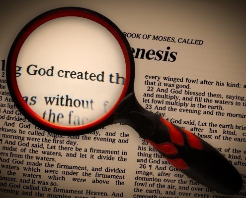 a magnifying glass focusing in on the words in Genesis 1:1