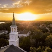 Aerial view of historic church steeple and sunset