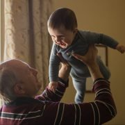 grandfather holding smiling baby
