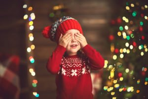 child covering eyes waiting for a Christmas suprise