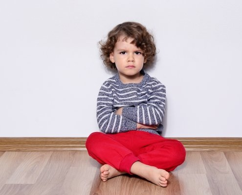 Preschool aged boy sitting by himself on floor looking angry.