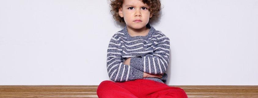 Preschool aged boy sitting by himself on floor looking angry.