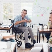 A group of adults, including a man in a wheelchair, are laughing together in a meeting.