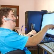 Man in a wheelchair using a computer with touchscreen