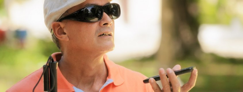 blind man using Digital Assistant and Ease of Access functions on mobile phone