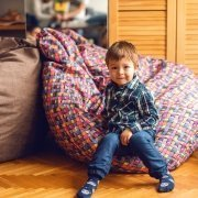Little boy sitting on a bean bag seat and smiling.