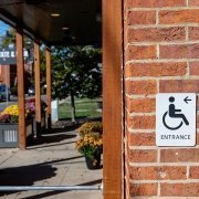Outside of a building showing a sign for a wheelchair entrance