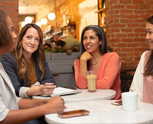 a group of ladies smiling and talking together in a coffee shop