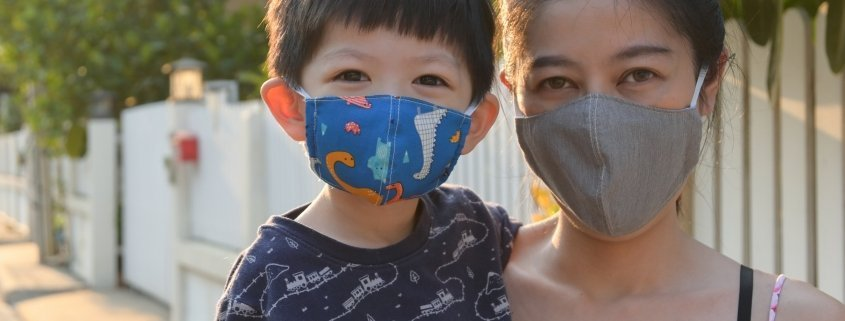 A mother and preschool aged son outside wearing masks.