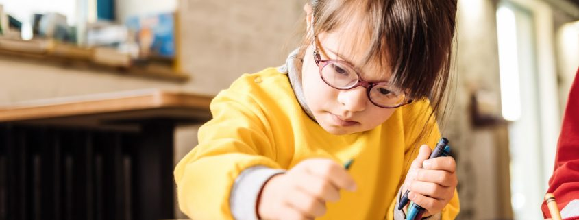 A young girl with Down sydrome coloring alongside a peer at a table