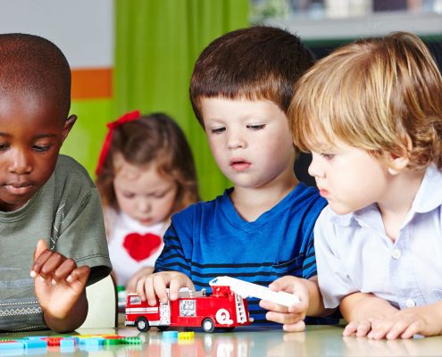 preschool aged kids sitting and playing side by side at a table