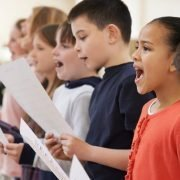 Group of elementary aged children holding sheet music and singing together
