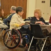 Woman using a wheelchair at a table talking with other ladies