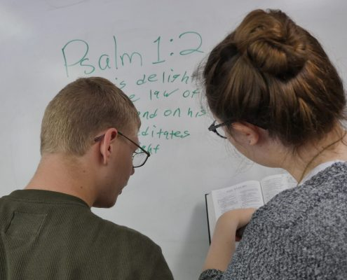 teens writing Bible verse on whiteboard