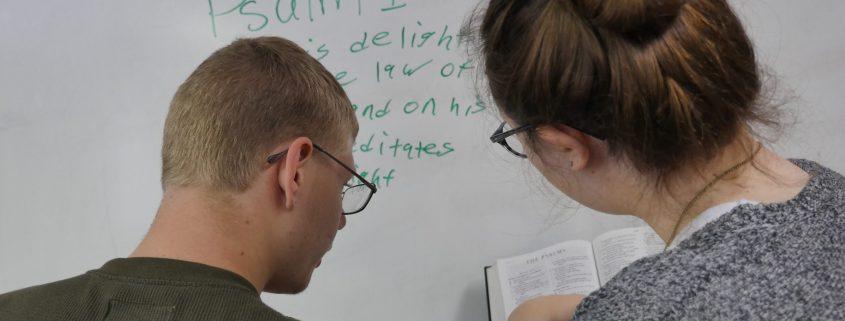 teens writing Bible verse on whiteboard