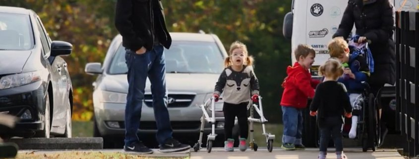 Young kids with disabilities and siblings moving from their cars into church