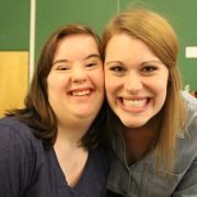 Two smiling friends, one with Down syndrome, at a Friends for Life ministry event