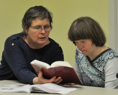 a woman shows an open bible to a woman with Down syndrome at Bible study with her