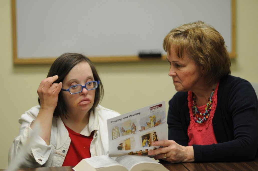 An adult woman with a disability and a friend learning together at a bible study.