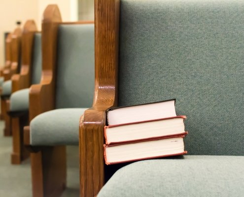 hymnal and Bible stacked on an empty church pew