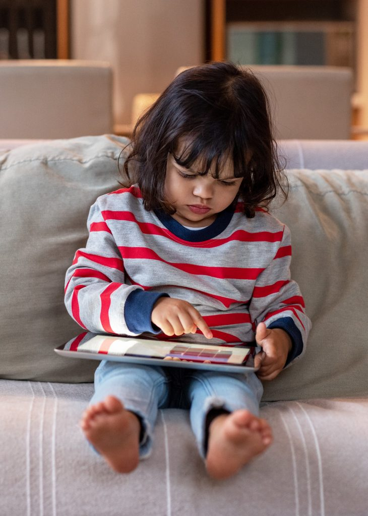 Little girl sitting on her sofa using a digital tablet