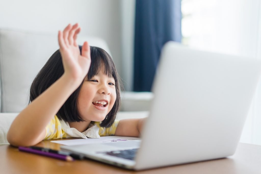 student waving while watching something on a laptop