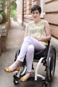 Chelsey Lauren sitting outside in her wheelchair smiling at the camera