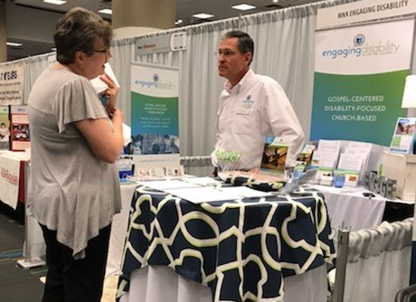 Joel Wallace talking with someone at General Assembly booth