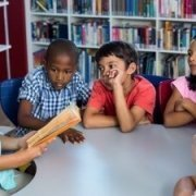 a group of elementary aged children sitting at a classroom table listing to teacher read a book