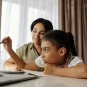 mom sits beside daughter working at computer