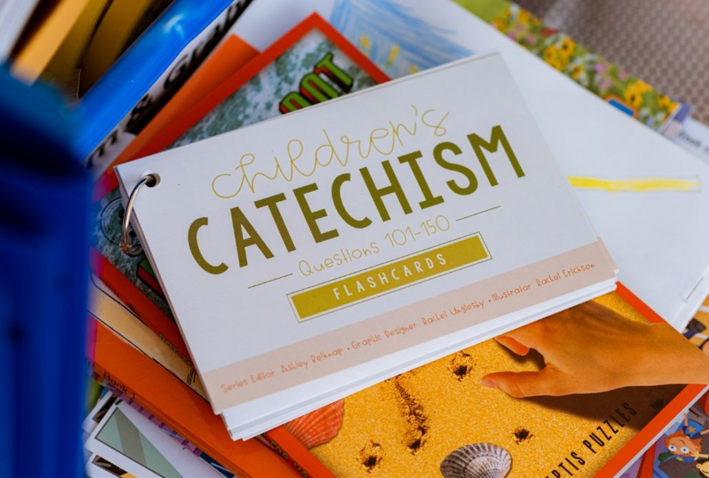 Children's Catechism Flashcards 101-150 sitting on top of a stack of books