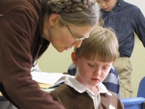 teacher checks in with elementary aged student in class to help him understand lesson