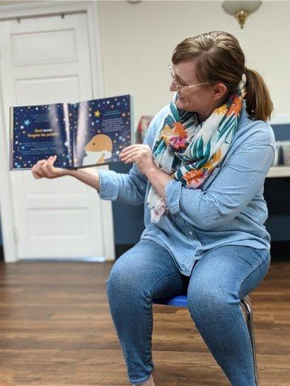 Team member Kara Whittaker reading a book to a class
