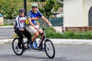 Kevin Daane riding a two seater bike with a young man